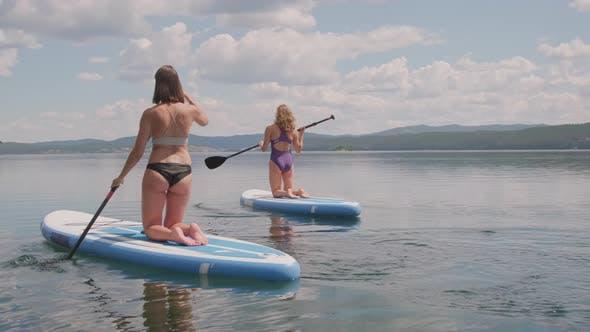 Women Practicing Paddle Surfing on Lake