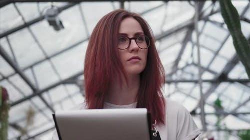 Eine junge Frau mit Brille, schaut in die Ferne und macht sich Notizen.