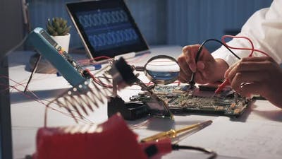 View of Woman's Hands Testing Motherboard in Laboratory