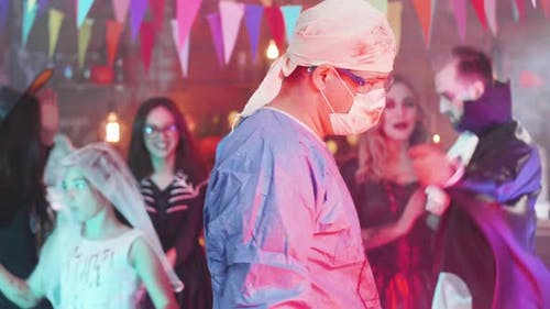 Slow Motion Shot of a Man in Psycho Mad Surgeon Costume at a Halloween Party
