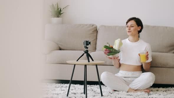 Eine Pretty Fit Frau mit frischem Saft macht ein Video