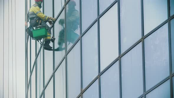 Thumbnail for A Man Worker in Yellow Work Clothes Hanging on Ropes and Wipes the Exterior Windows of a Business