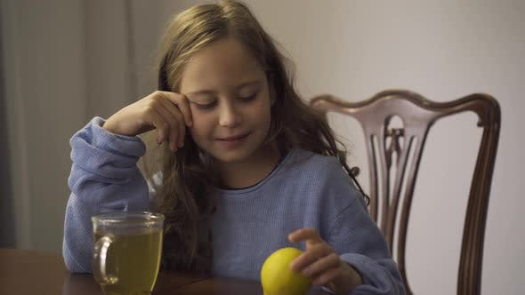 Thumbnail for Close-up of Little Girl Holding Lemon While Drinking Herbal Tea. Child Sitting at the Table at Home