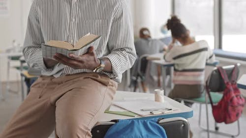 Midsection of Teacher Reading Book in Class