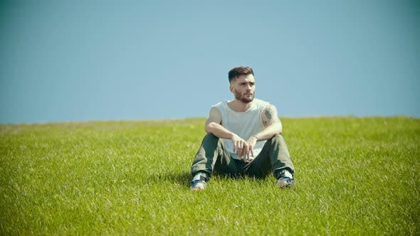 Thumbnail for A Young Man with Tattoos Sitting on a Bright Green Grass