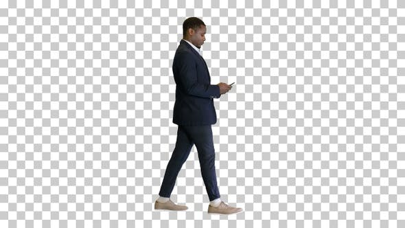 Young African American man walking and texting, Alpha Channel