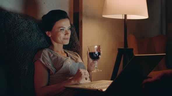 Thumbnail for Woman Drinking Red Wine with Notebook. Girl Looking Laptop with Wineglass.