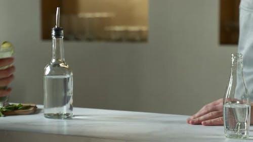 Closeup Man Bartender Serves the Client a Mojito Cocktail