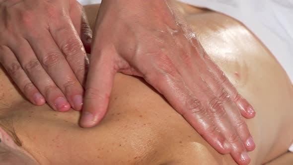 Thumbnail for Hände des professionellen Masseurs gleiten auf der Schulter der weiblichen Klientin