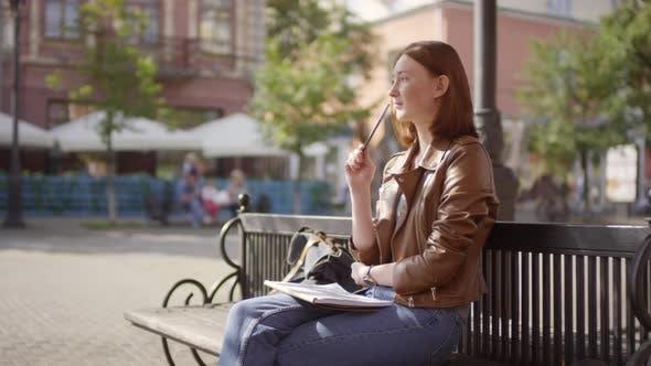Pensive Teenage Girl Sketching Outdoors