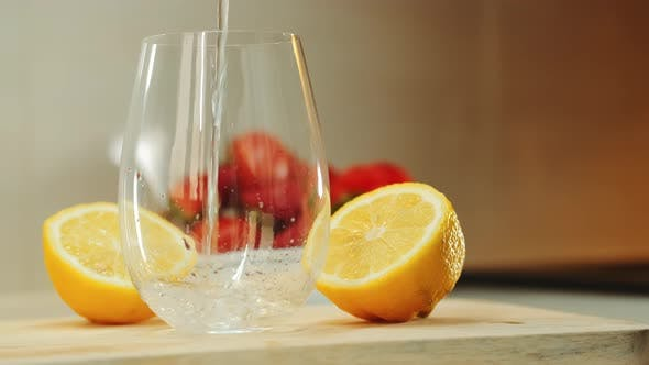 Thumbnail for Empty Glass Between Two Part of Cut Lemon on Wooden Cutting Board