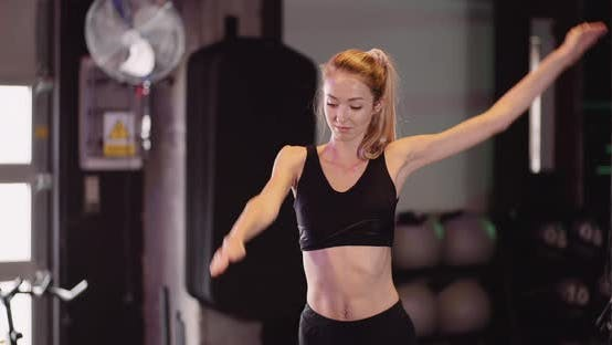 Young Woman Wearing Sportswear, Exercise, Stretch at Gym Modern Fitness Studio.
