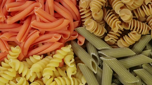 Thumbnail for Mehrfarbige Pasta Drehen in Zeitlupe Draufsicht. Rotation der farbigen Spirale Pasta. Haufen von