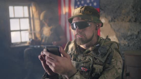 American Soldier Browsing Smartphone During War