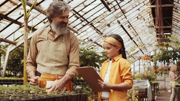 Thumbnail for Joyous Granddad and Little Girl Posing for Camera in Greenhouse Farm