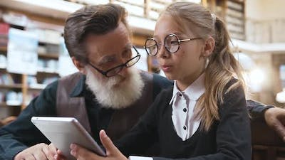 Grandfather with Glasses Talking with His Smiling Teen Granddaughter and Using Ebook