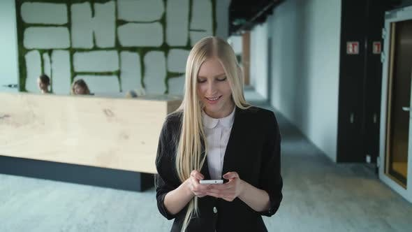 Thumbnail for Young Formal Woman Using Smartphone in Office. Stylish Blond Woman in Jacket Standing in