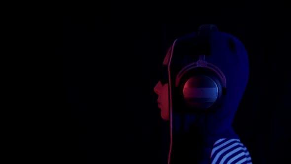 Profile of Teenager in Hoodie Sunglasses and Headphones in Darkness