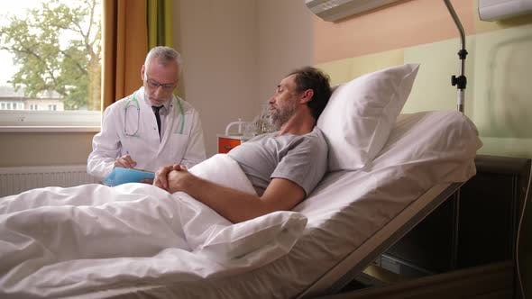 Thumbnail for Elderly Doctor Talking To Sick Patient in Bed