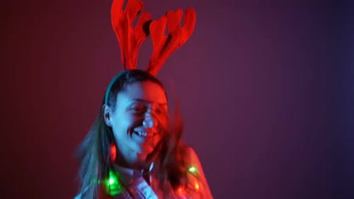 Young Woman in Christmas Mood Wearing Reindeer Antlers and Dancing