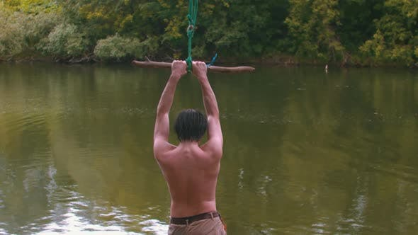 Cover Image for Young Man Swings on the Stick and Falling Down in the River