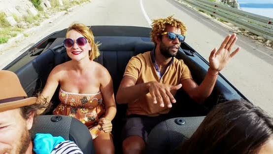 Blonde woman and black man riding in the back of convertible, color graded