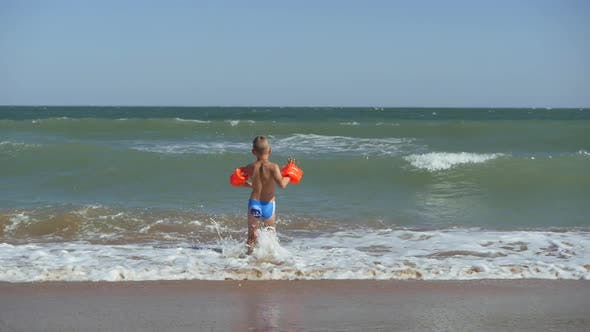 Boy Runs Into the Sea. Waves Wash Over the Beach. Child in Armbands on Vacation at Sea. The Child