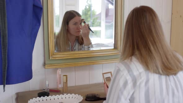 Thumbnail for Woman Putting on Foundation before Mirror