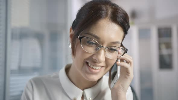 Thumbnail for Beautiful Female Office Worker in Glasses Makes a Client Call and Talks on the Phone