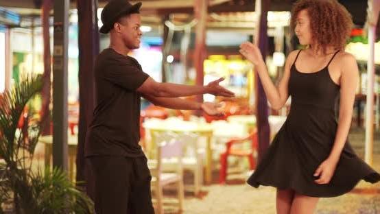 Black couple dances in front a festive restaurant