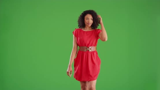 Thumbnail for Fashionable black woman in red dress walking toward camera on green screen