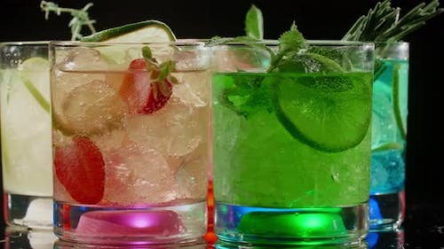 Cold Colorfull Cocktails are Spinning on the Black Background Lightened Glasses Refreshment Drinks