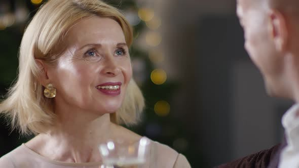 Thumbnail for Happy Caucasian Lady Chatting to Partner at Christmas Party with Champagne