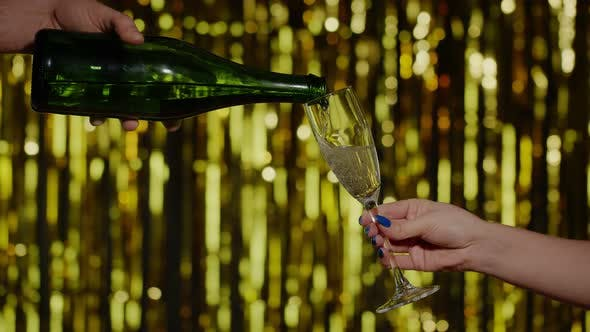 Thumbnail for Champagne Alcoholic Drink Is Poured From Bottle Into Drinking Glasson Gold Background in Slow Motion