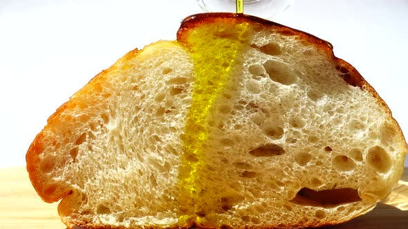 Olive Oil Pours on a Piece of Bread