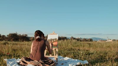 Young girl paints the picture on canvas in the countryside
