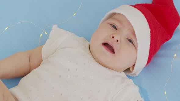 Thumbnail for Funny Little Baby Smiling of the 2021 Year. Cute Infant Boy Wearing Santa Hat Lying on Sofa.