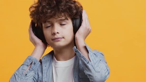 Close Up Studio Porträt des lockigen kleinen Jungen Genießen Musik in großen kabellosen Kopfhörern