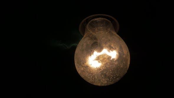Thumbnail for Swinging dusty light bulb in the dark 4K 2160p UHD video - Light bulb swing horror scene 4K 3840X216
