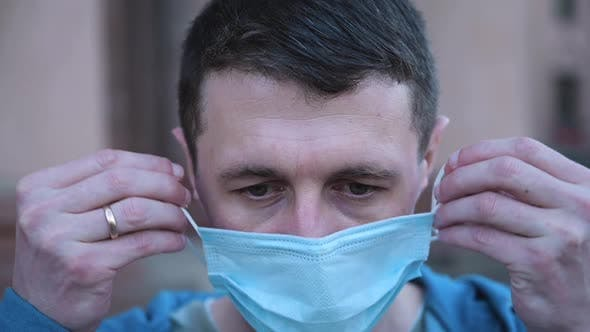 Close Up Portrait of Caucasian Man Putting Medical Mask on Face