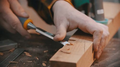 Woodworker Cutting Out the Recess on the Wooden Block with a Chisel