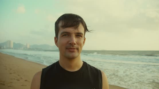 Portrait of a Young Caucasian Man Looking Into the Camera Along the Backdrop of the Beautiful Sea