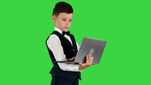 Thumbnail for Concentrated Boy in a Bow Tie and Waistcoat Using Laptop Computer While Standing on a Green Screen