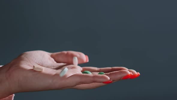 Thumbnail for Pills of Different Colours Fall Into Hand with Red Manicure