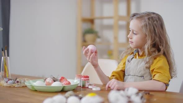 Thumbnail for Niedliches Mädchen Blick auf dekorierte Ostereier