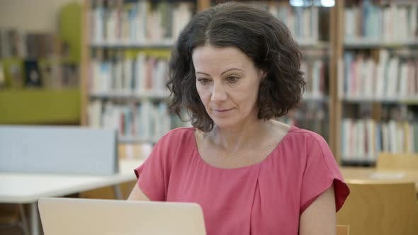 Thumbnail for Concentrated Caucasian Woman Working with Laptop at Library