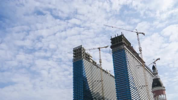 Construction of a Modern Skyscrapers Using Tower Cranes. Timelapse, Moving Clouds on Blue Sky