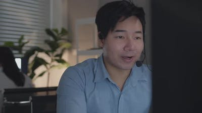Friendly Asian Customer Service with headset working on desktop computer talking with a customer