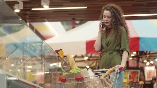 Cheerful Woman Having Phone Talk in Market