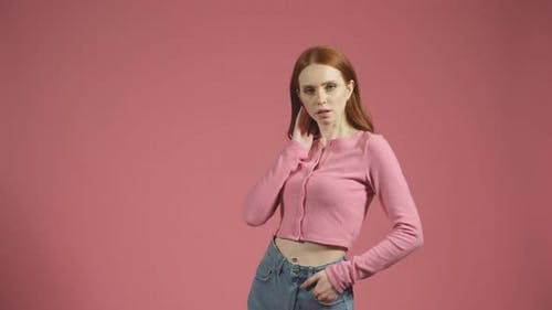 Serious Young Woman with Long Red Hair Poses for the Camera on an Isolated Pink Background